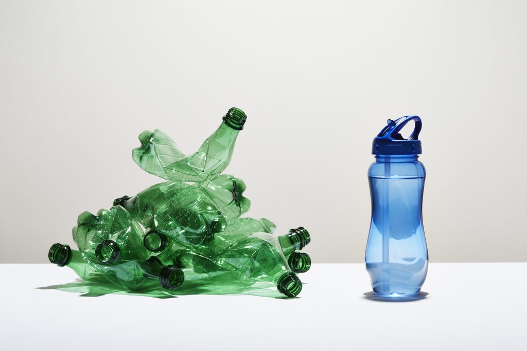 A heap of disposable water bottles next to a reusable water bottle