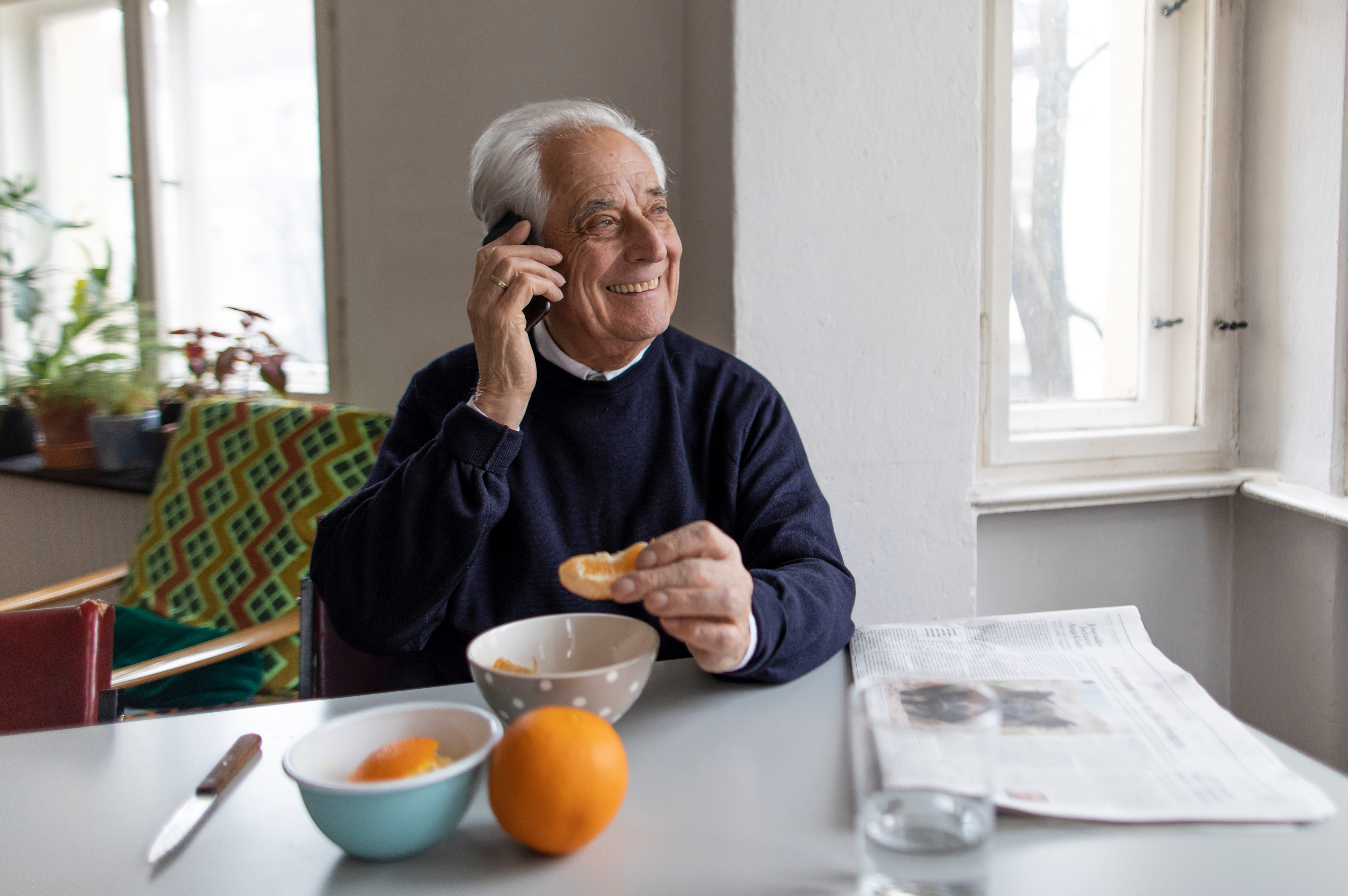 Smiling senior man on cell phone at home