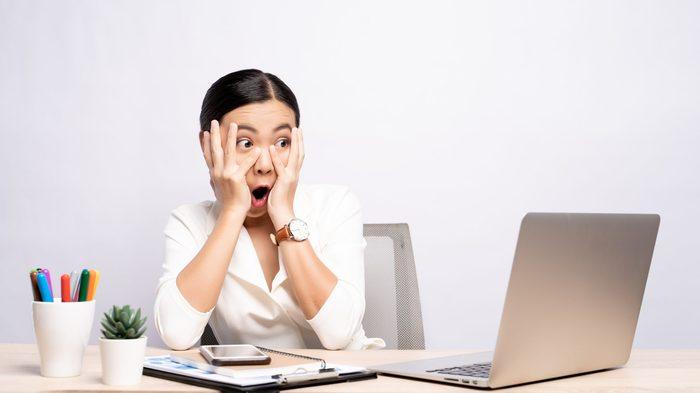 Shocked Businesswoman Using Laptop At Desk Against White Background