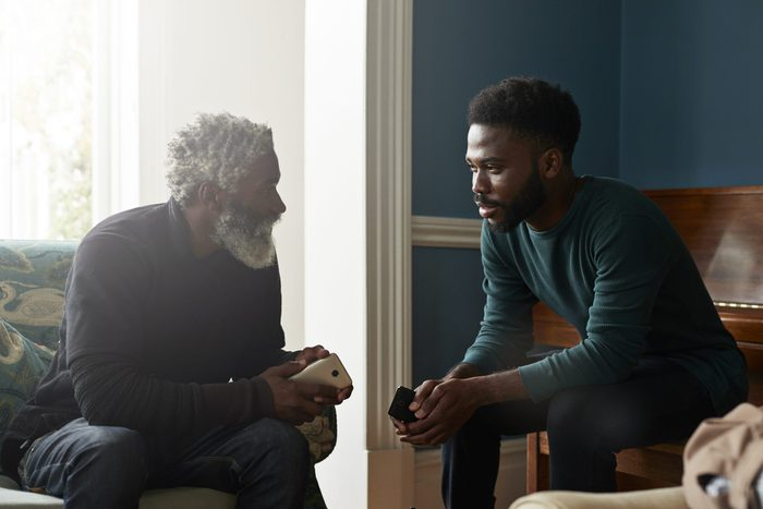 Male friends talking while sitting in living room