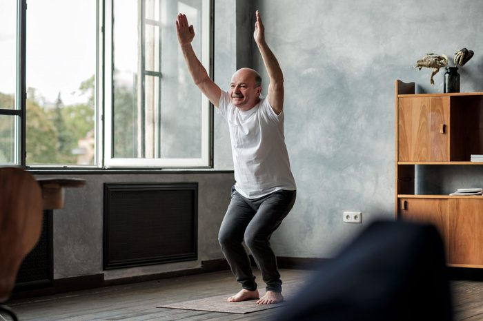 Man practicing yoga indoors at living room doing Chair pose or Utkatasana