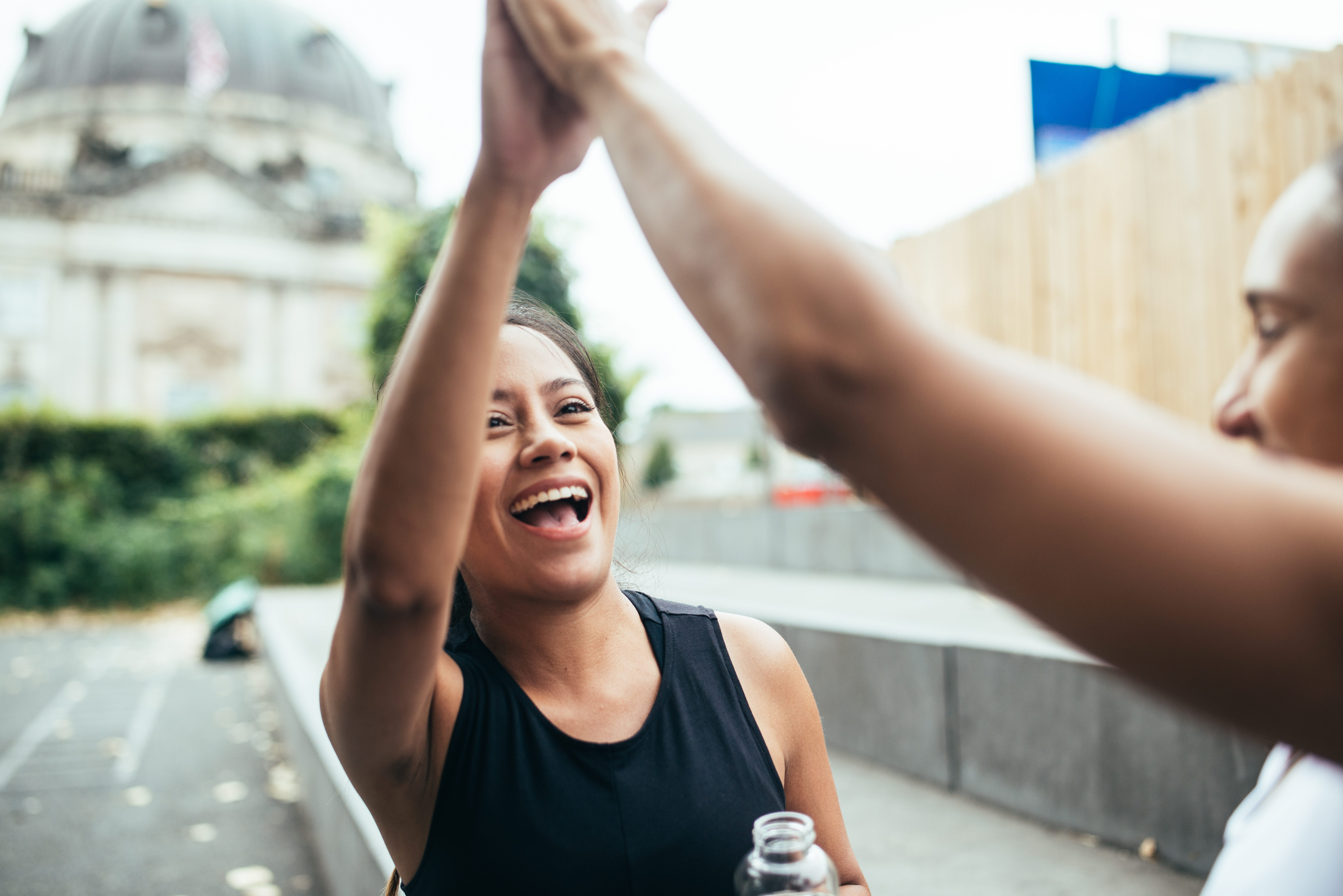 Two women giving high five after workout challenge.