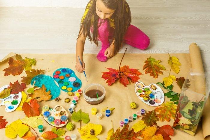 Little girl painting on autumn yellow leaves with gouache, kids arts, children creativity, autumn art.