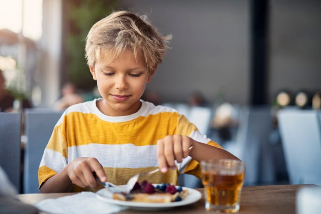 Little boy eating breakfast crepes with fruits