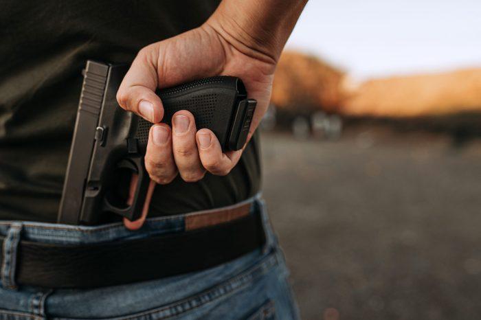 Man holding hidden short gun in his hand.