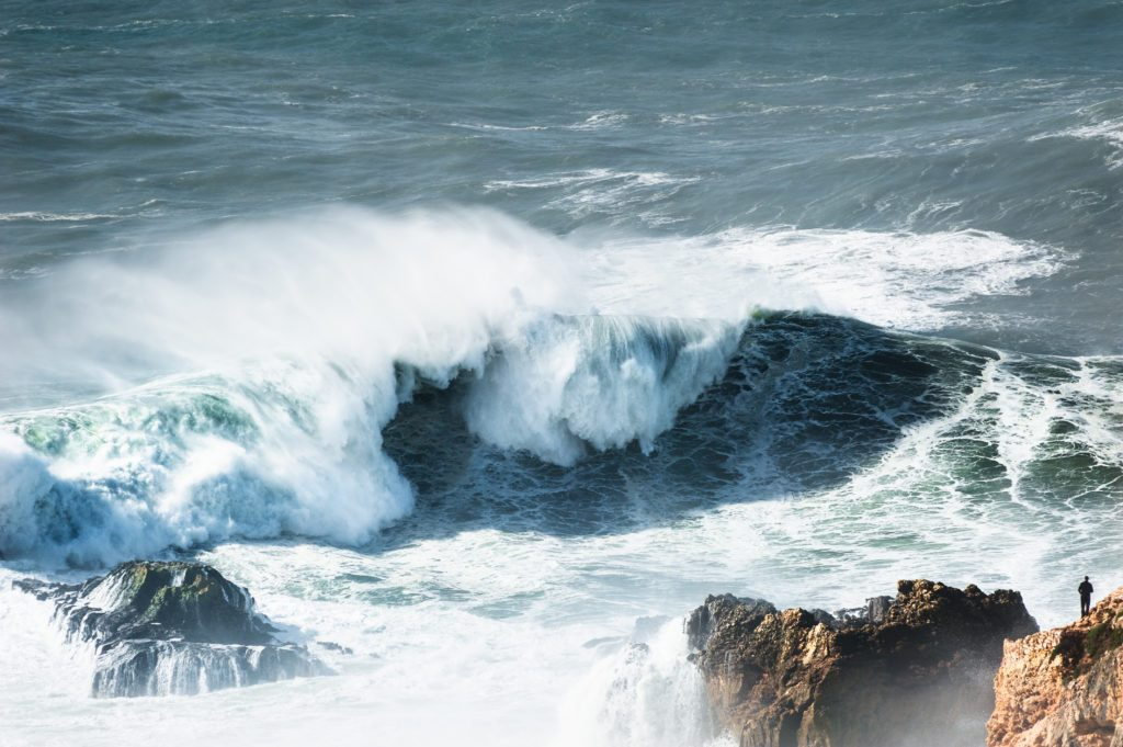 Man watching big waves in Nazare, Portugal.
