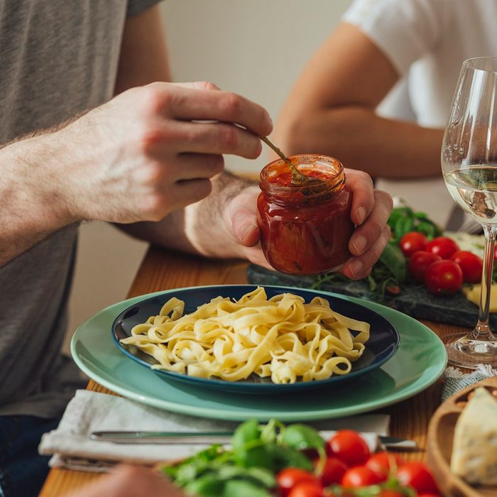 Hands of unrecognisable man holding a jar and putting sauce on his pasta at dinner.