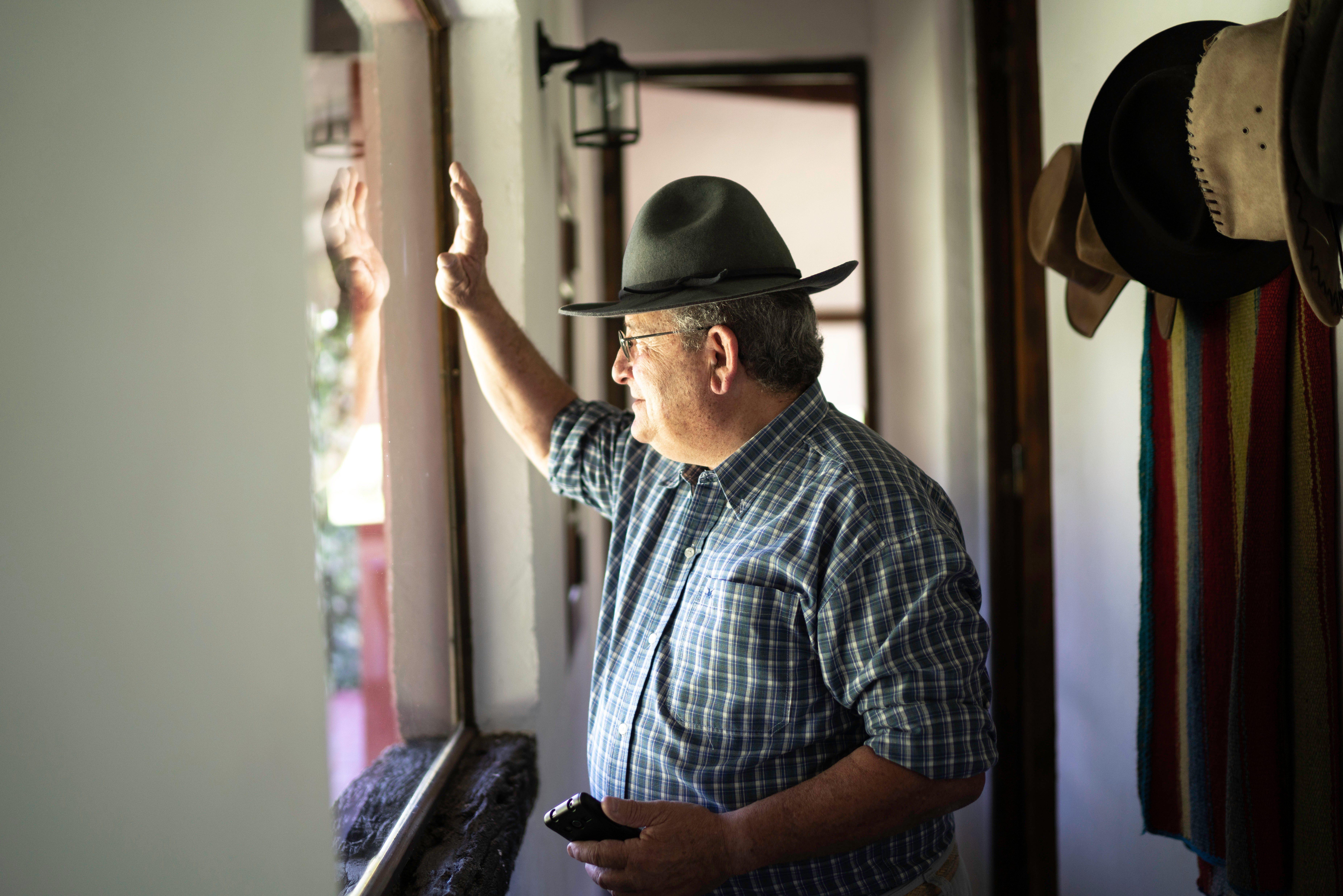Senior man waving through the window