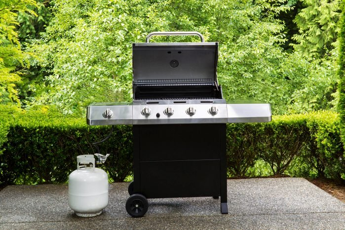 Large outdoor bbq cooker with lid in open position on home concrete patio