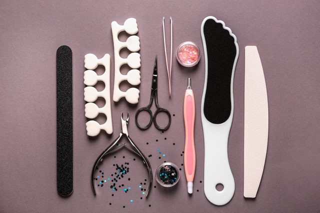 Set of pedicure tools on grey background
