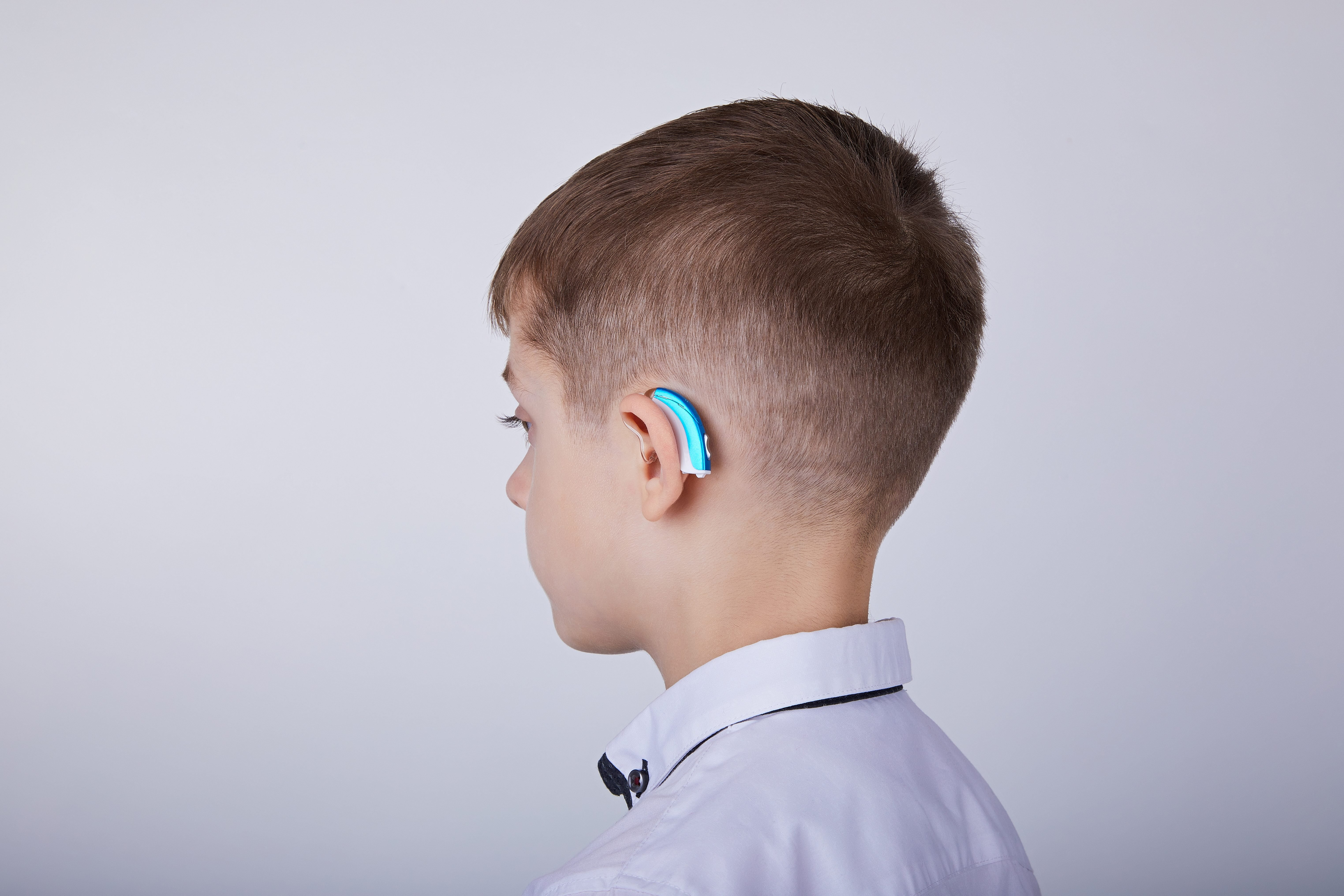 Young boy wearing a hearing aid.