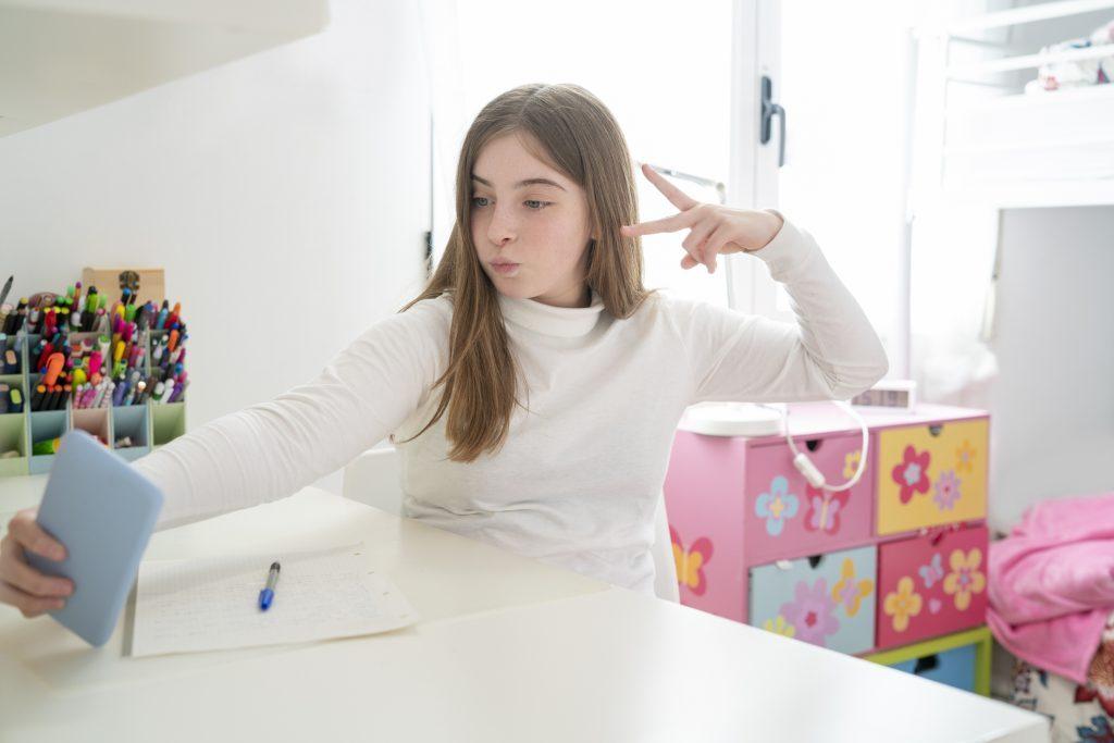 Teenager student girl selfie with smartphone at homework