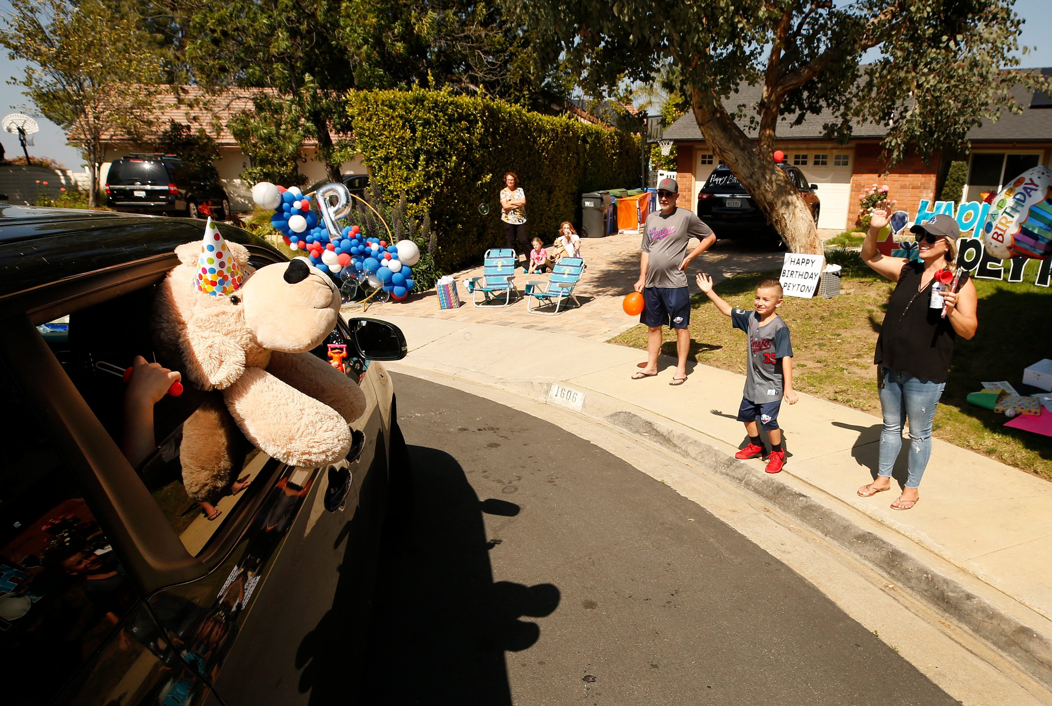 Peyton Buss waits for cars full of fellow team members from his 2019 Conejo Valley Little League All Star Baseball Team to drive by his home in Thousand Oaks to celebrate his 8th birthday amid the coronavirus Covid-19 pandemic.