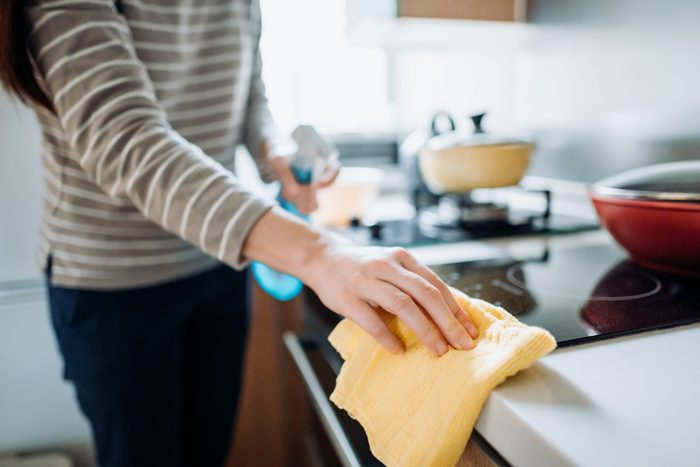 Cropped shot of a young woman cleaning the kitchen counter with cleaning spray and cloth at home during the day