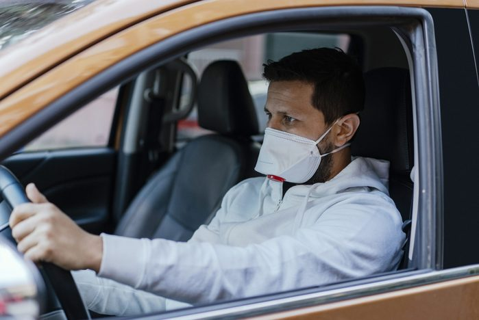 Man driving his car with a protection mask in the city