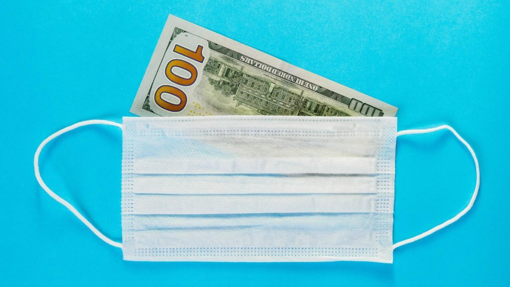 one hundred dollar bill under a surgical mask. blue background