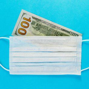 one hundred dollar bill under a surgical mask. blue background