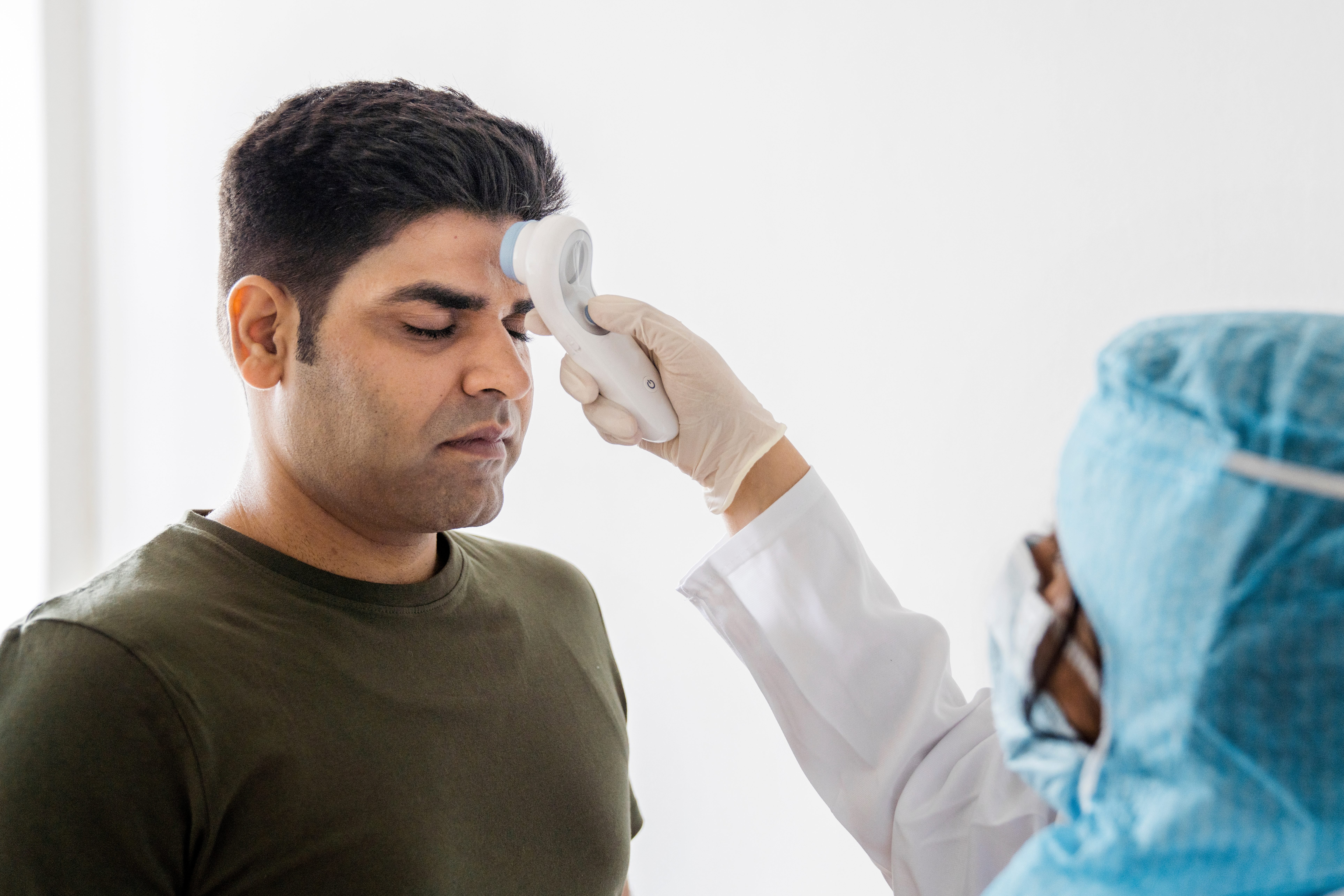 Healthcare worker scanning fever of patient