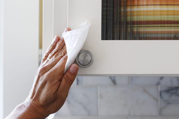 Man Cleaning Kitchen Cabinet Door Handle With Disinfectant Wipe