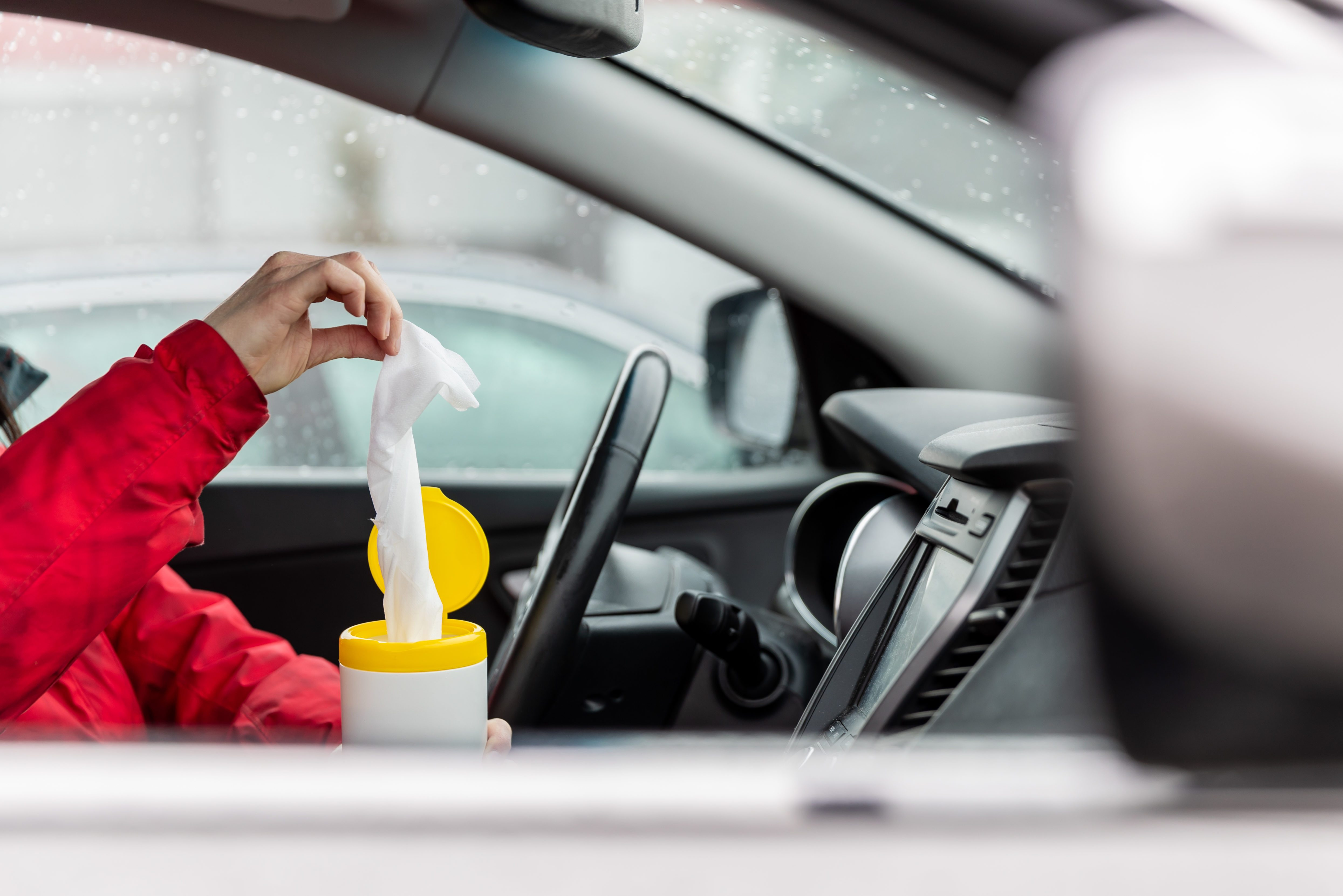 Woman using wet wipes to clean the steering wheel of a car