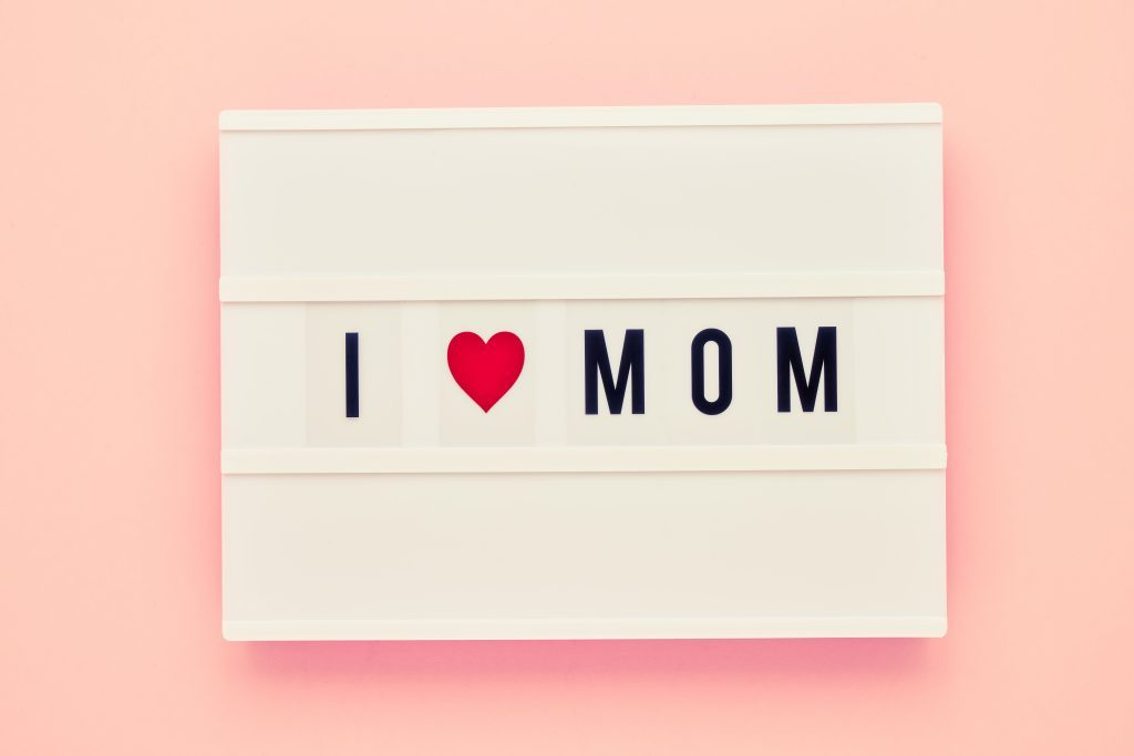 I LOVE MOM written in light box on pink background. Mothers Day celebration concept. Top view, copy space