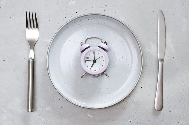 breakfast time concept with alarm clock plate, fork, knife, spoon,