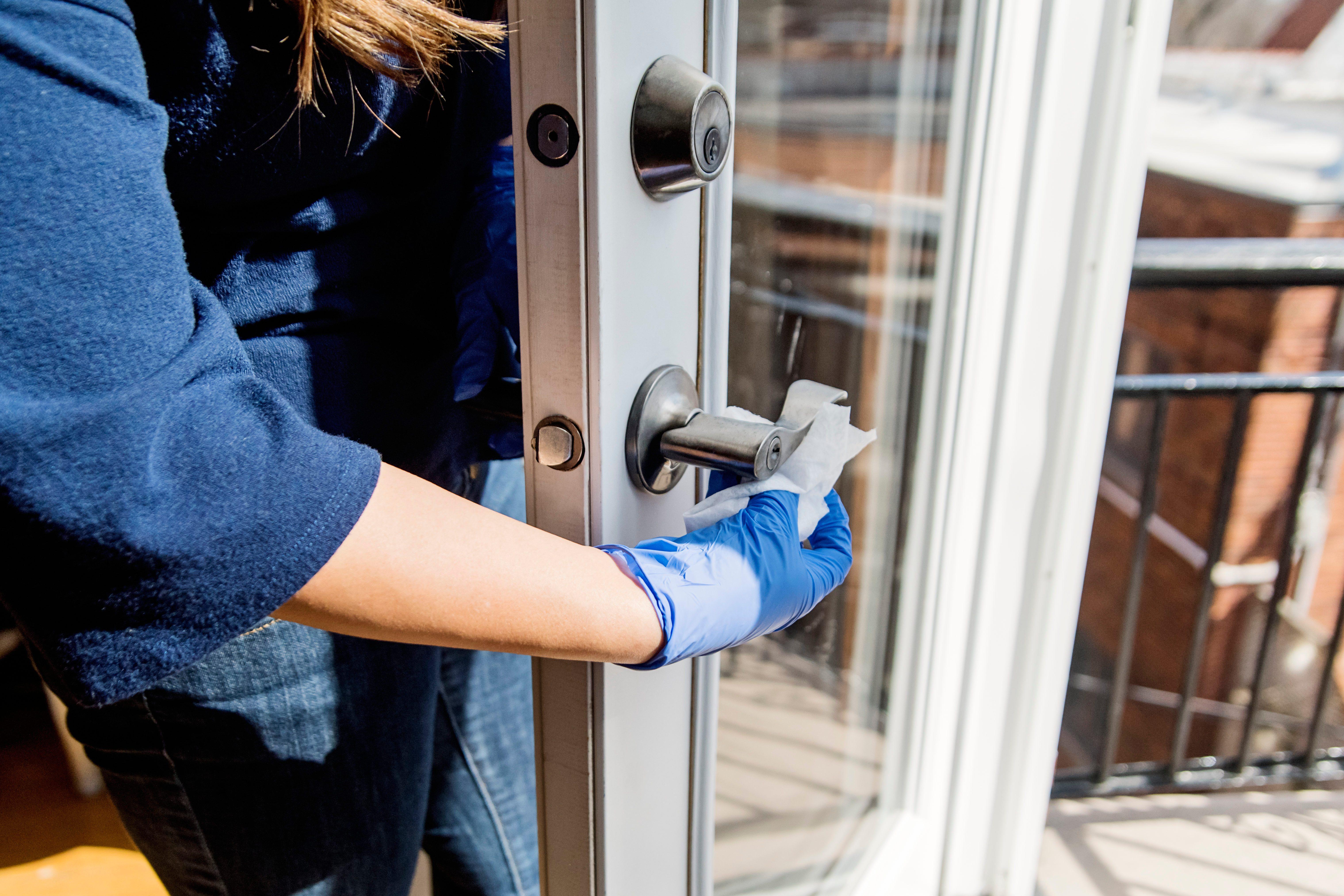 Woman with glove wiping door handle.