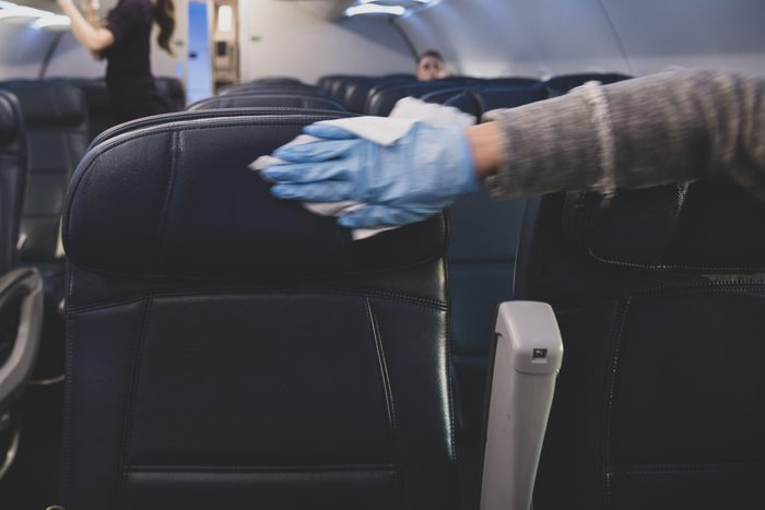 Passenger disinfecting airplane seats after boarding flight