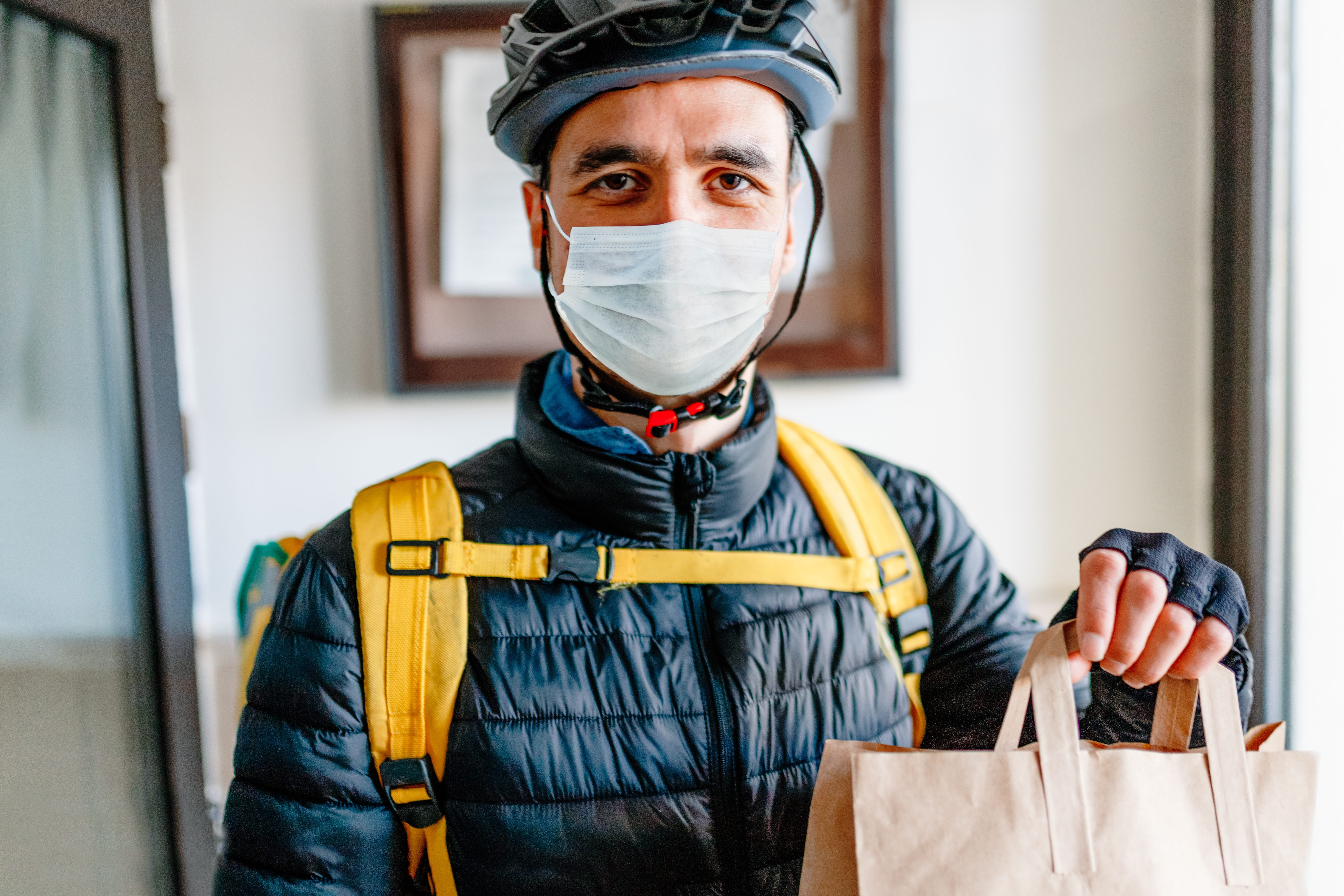 Young man as a courier delivering food