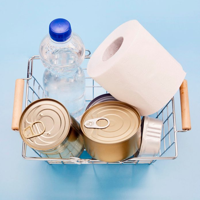 Still life of canned food, bottle of mineral water and toilet paper in shopping basket on blue background