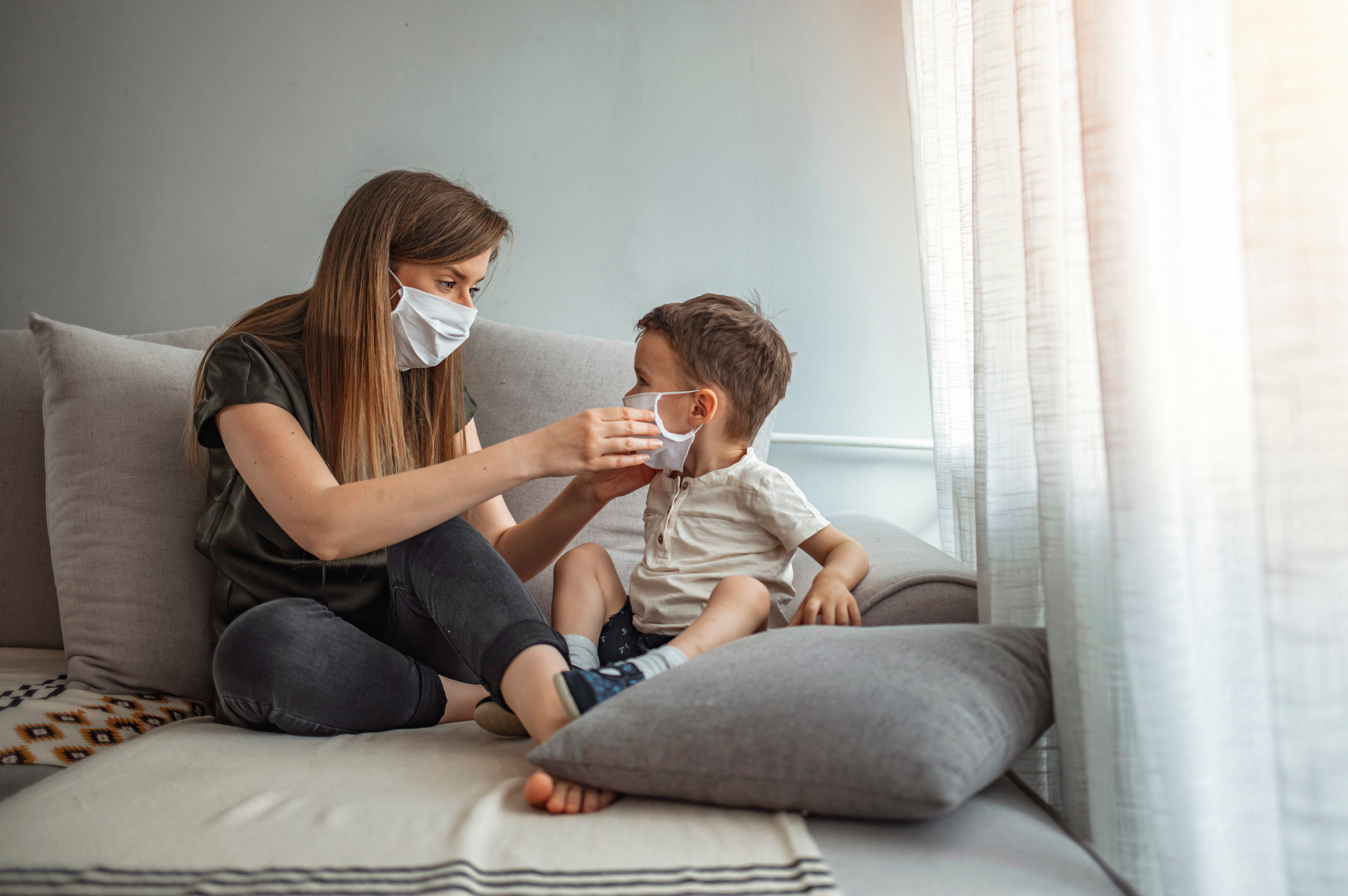 Mother putting protective face mask on her child.