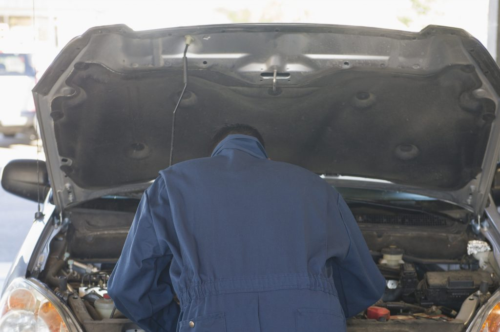 Hispanic worker working on automobile engine