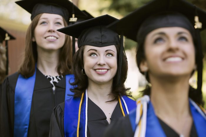 College graduates standing together looking up