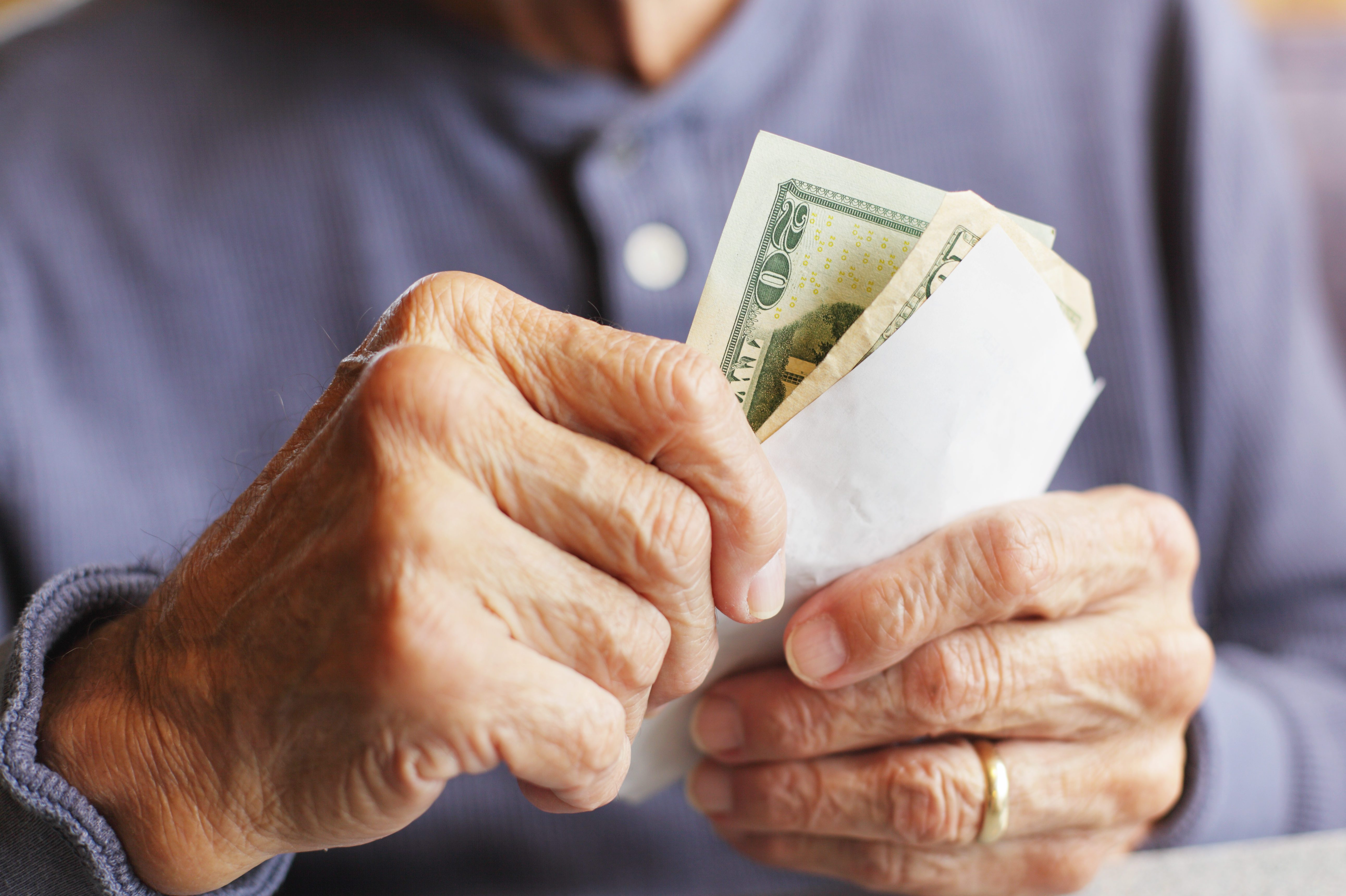 Senior Man Hands Holding Money and Breakfast Bill