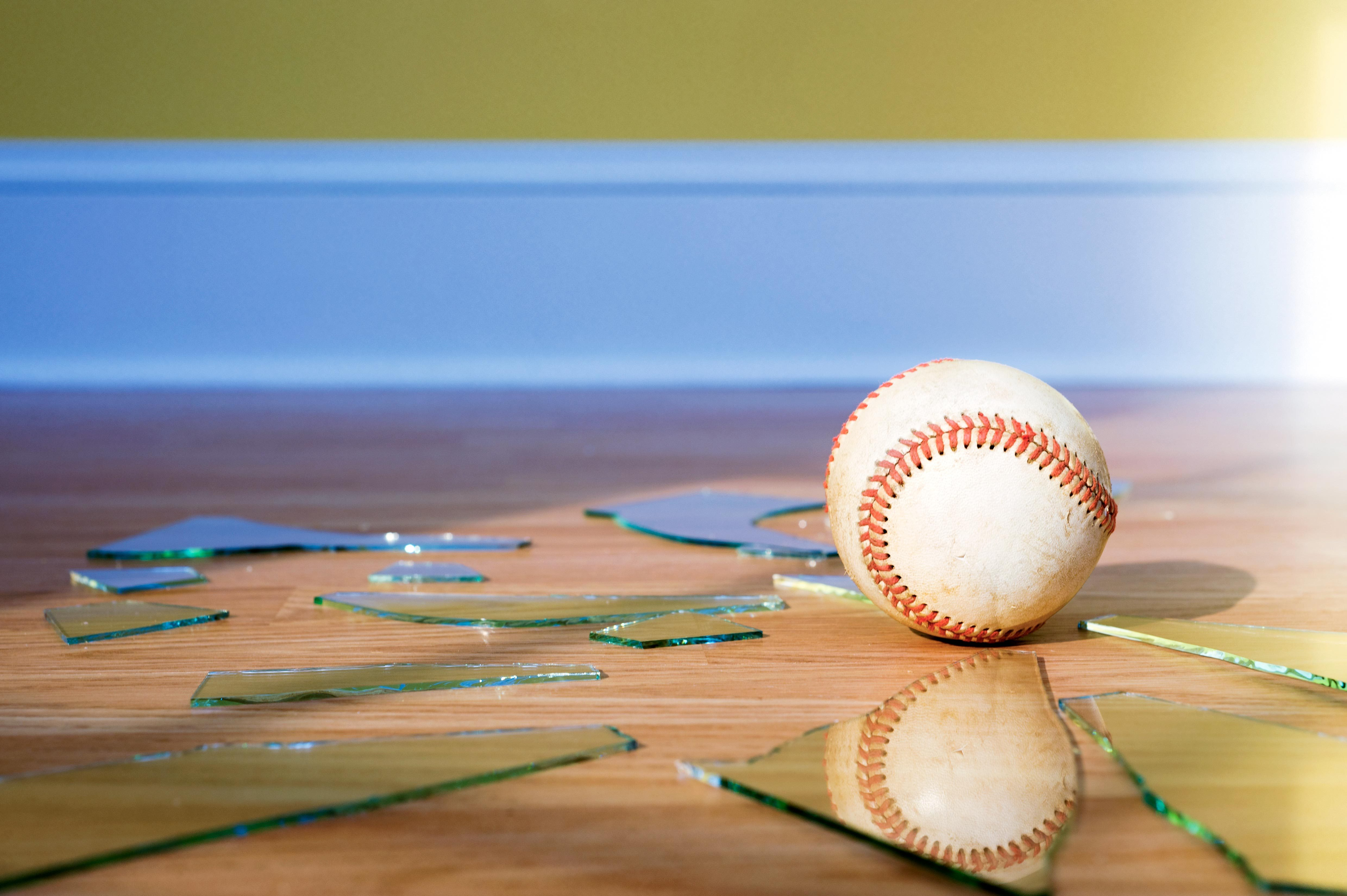 baseball on the floor among broken shards of glass