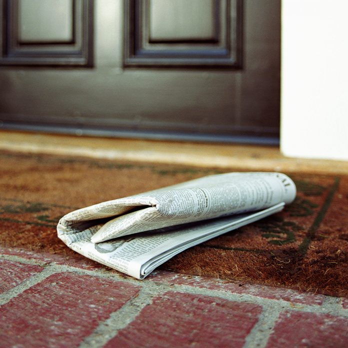 Newspaper on front step of house