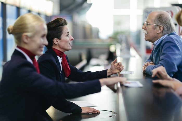Senior Man At Airport Check-In Counter