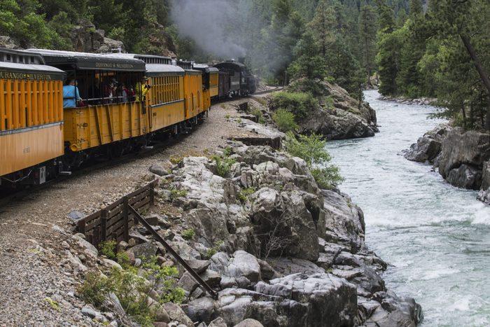 Durango and Silverton Narrow Gauge Railroad Steam Engine travels along Animas River, Colorado