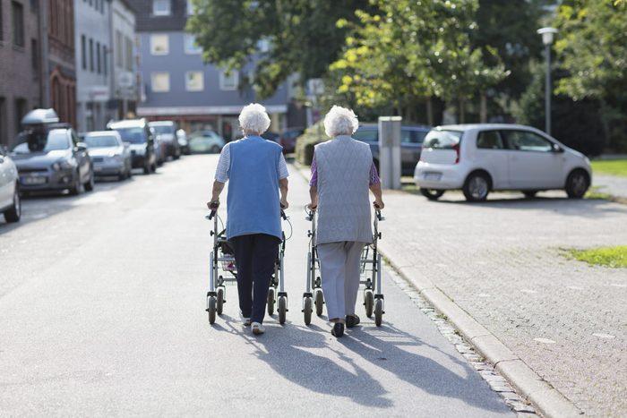 senior women together walking with walker