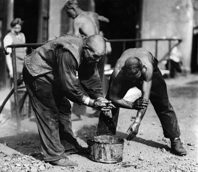 Workers at an engineering works washing themselves with water from a bucket after having finished their workday - 1930- Photographer: Seidenstuecker- Published by: 'Tempo' 04.04.1930Vintage property of ullstein bild