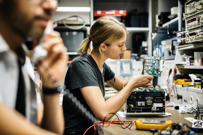 Female Technician Working On Conductor Board