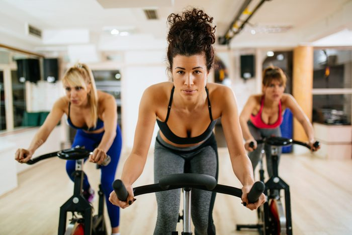 Sporty women exercising on exercise bike at modern gym.