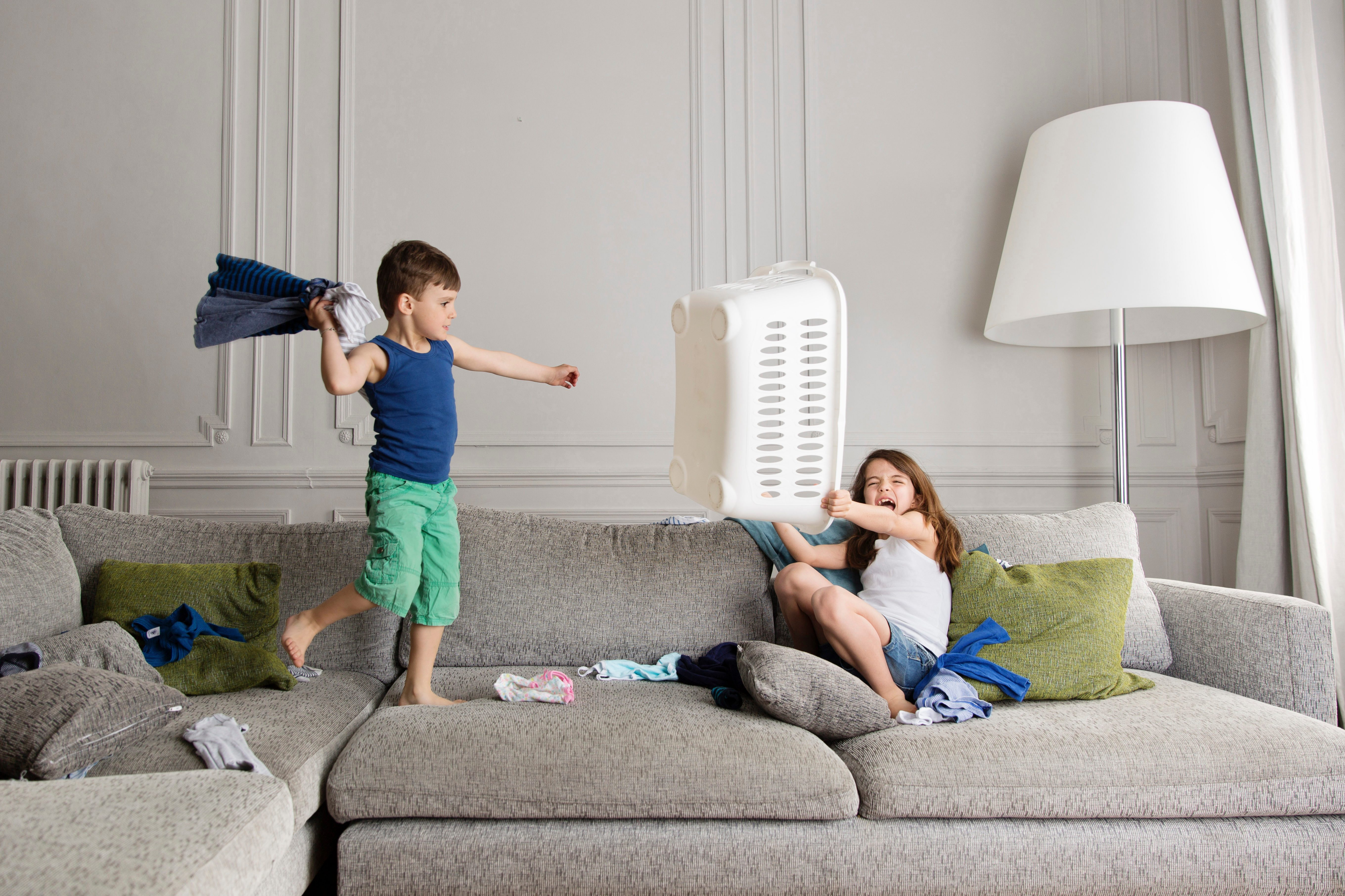 Little boy standing on the couch fighting with laundry while his sister protecting herself with laundry basket