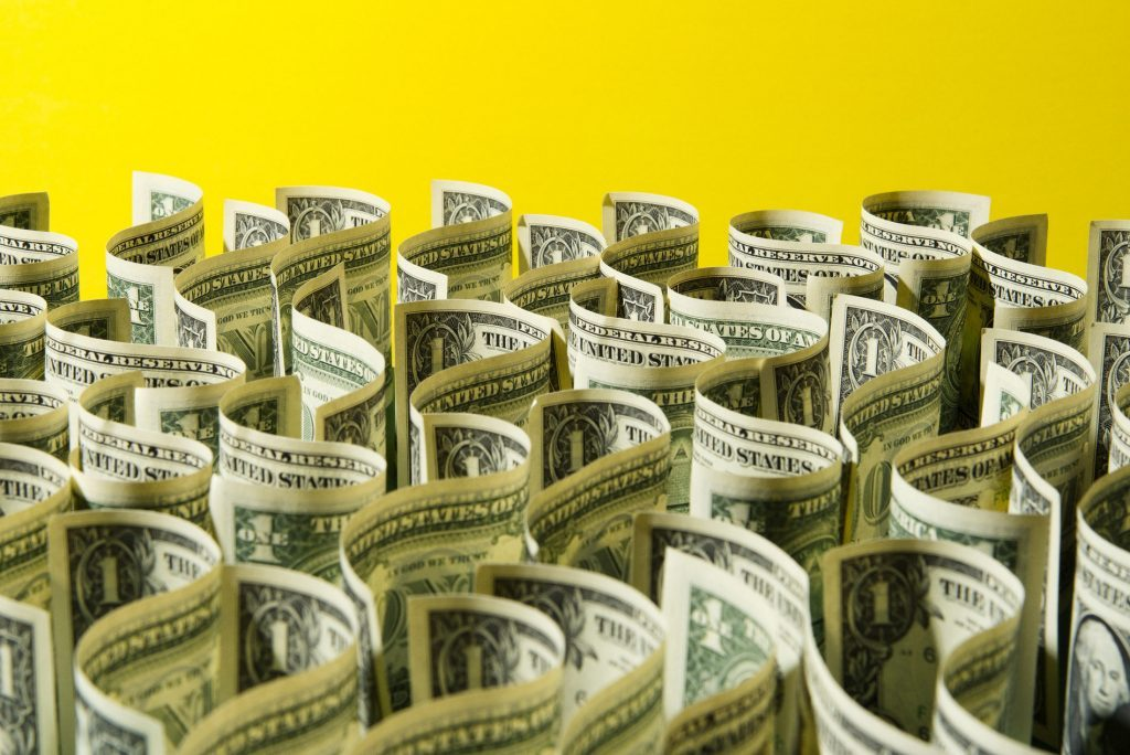 Sea of US 1 dollar bills on yellow background