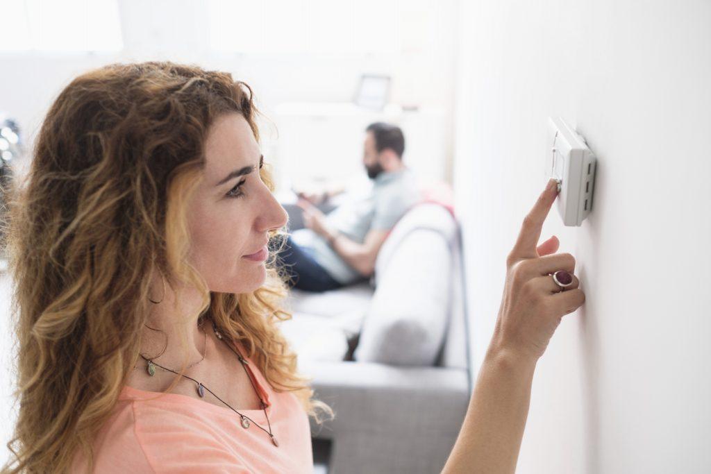 Mid-adult woman adjusting thermostat