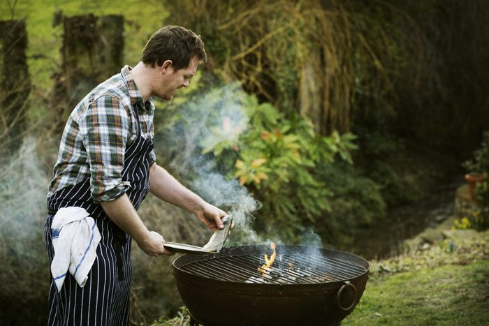 Chef standing in a garden, grilling fish on a barbecue.