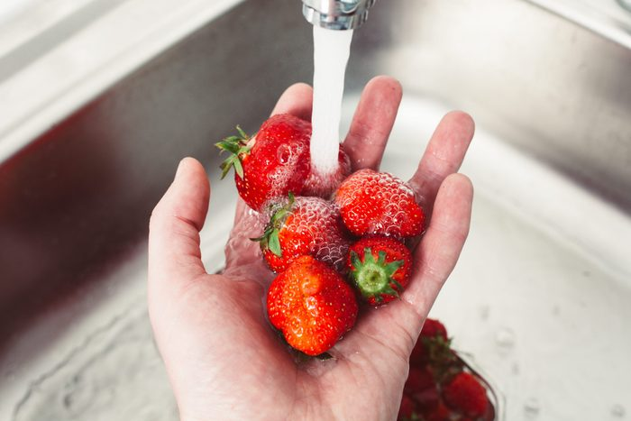 Strawberries in hands under the water. Pure fruit is health