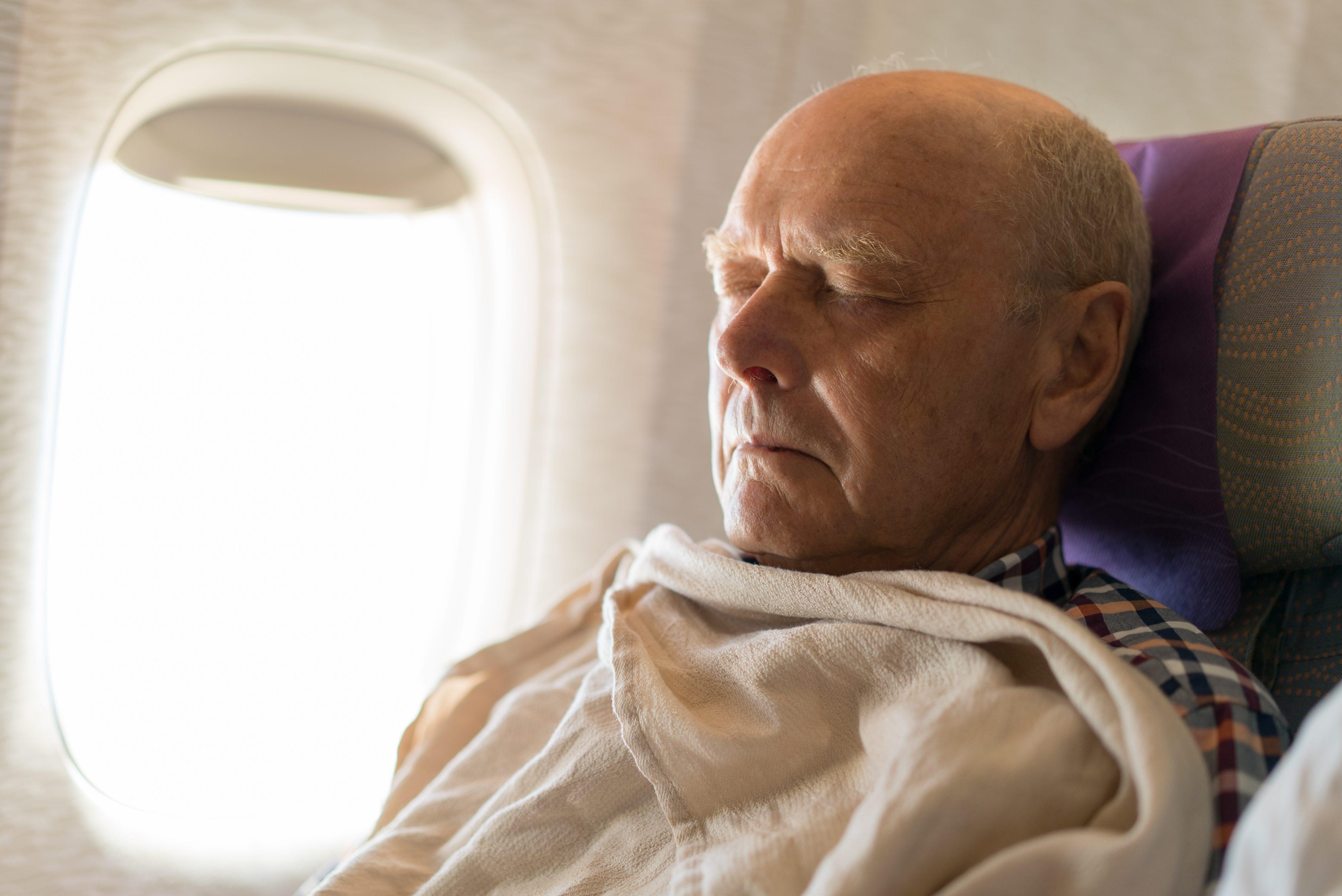 Seniors Taking on the World, man sleeping in plane