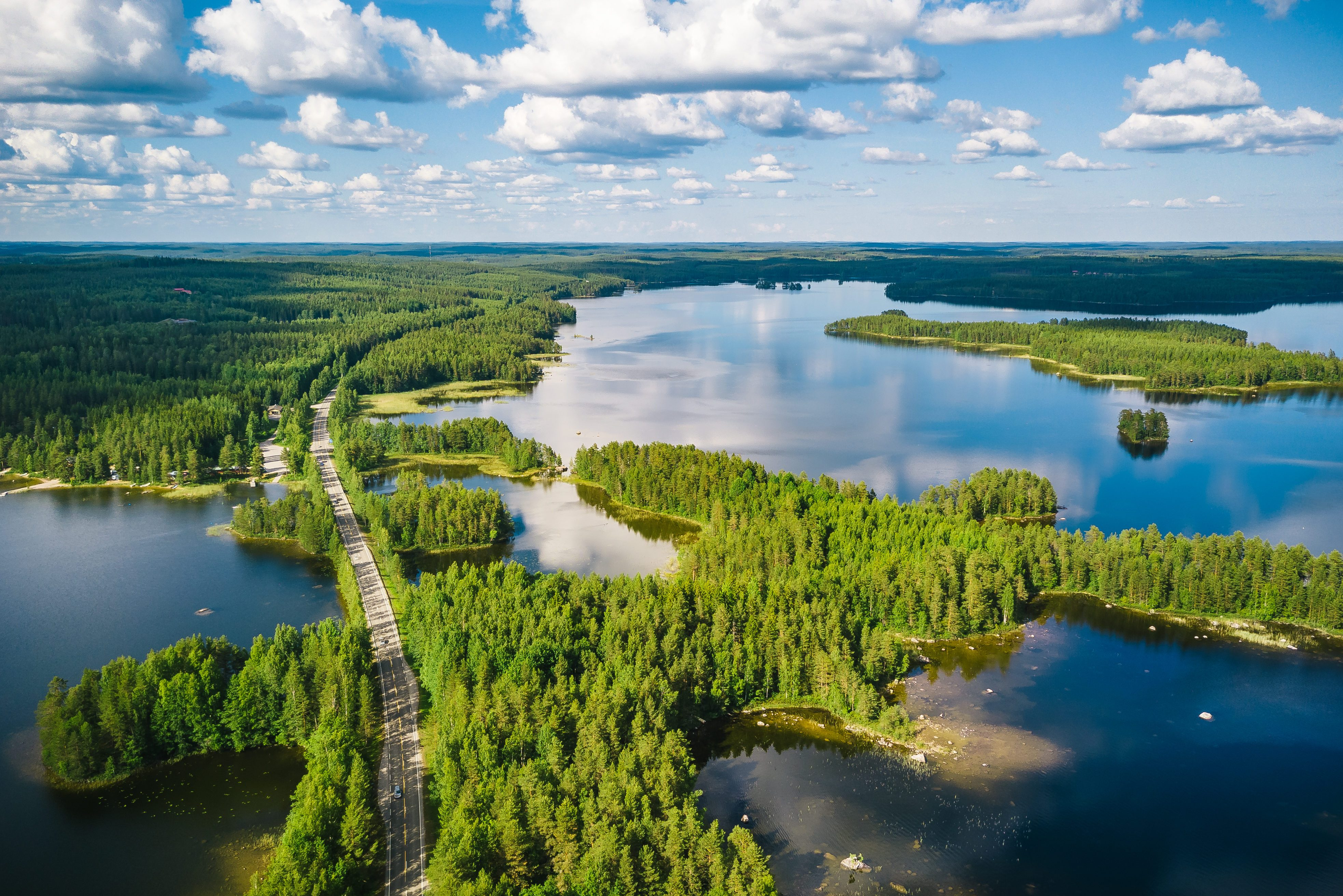 Aerial view of a winding road passing through forests & lakes in Finland on a summer day