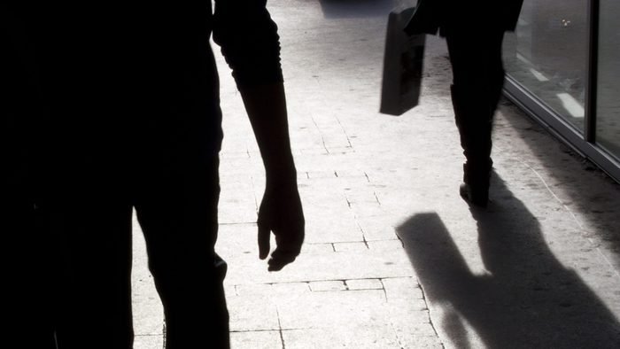 Blurry silhouette and shadows of two person walking